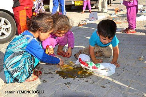Turkmen refugee children eating  eggs from the floor